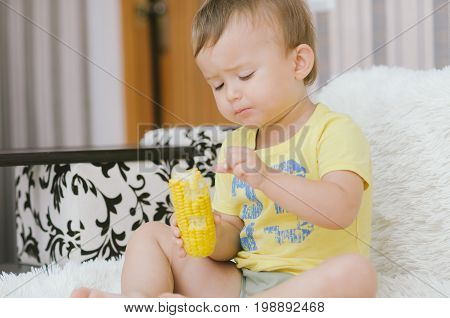Child In A Yellow Shirt Eating Corn