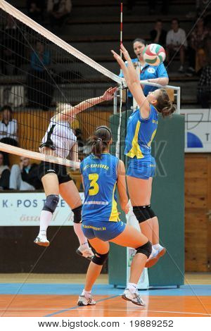 KAPOSVAR, HUNGARY - OCTOBER 10: Zsanett Pinter (R) blocks the ball at the Hungarian NB I. League woman volleyball game Kaposvar vs Veszprem, October 10, 2010 in Kaposvar, Hungary.