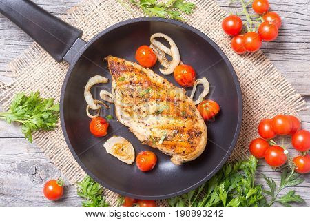 Grilled chicken breast with tomato parsley and onion
