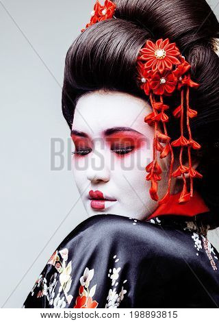 young pretty geisha in black kimono among sakura, asian ethno close up concept