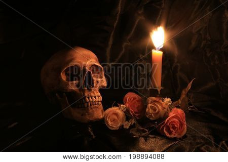 Human Skull With Roses Over Black Fabric Texture Background With Light Candle In Dim Halloween Night