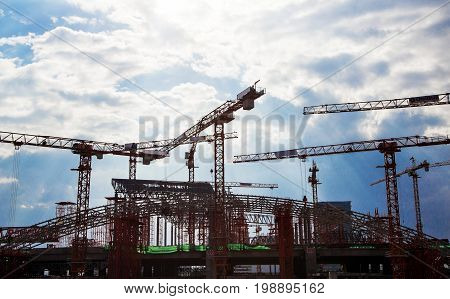 group of crane and stell structure in big construction high building on blue sky show urban city background