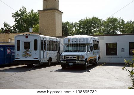 JOLIET, ILLINOIS / UNITED STATES - JULY 17, 2017: A bus and a van, belonging to the University of Saint Francis, are parked outside the Operations and Facilities building.