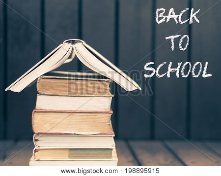 Retro style of book stacking. Open book hardback books on brown wooden background. Back to school concept.
