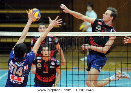 KAPOSVAR, HUNGARY - OCTOBER 15: Krisztian Csoma (R) strikes the ball at a Middle European League volleyball game Kaposvar (HUN) vs Bled (SLO), October 15, 2010 in Kaposvar, Hungary