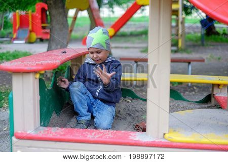boy playing in the sandbox park outdoor