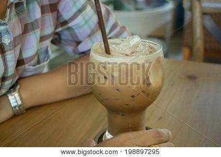 Hand on iced milk coffee stock photo