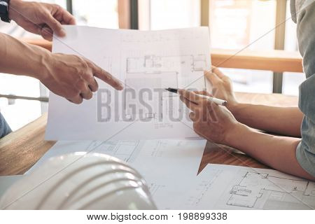 Image of engineer or architectural project Close up of Architects engineer's hands drawing plan on BluePrint and discussing to partner with Engineering tools on workplace Construction concept .