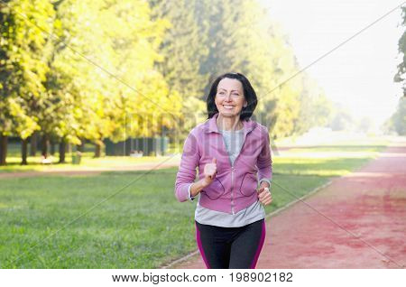 Portrait Of Elderly Woman Running In The Park