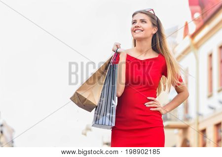 Attractive girl in red dress with shopping bags walking the city street. Fashion pretty cool young girl with shopping bags on old city background