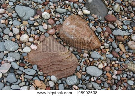 Small rocks and pebbles around larger rocks on the shore of Lake Superior.  Pictured Rocks National Lakeshore, Upper Peninsula of Michigan