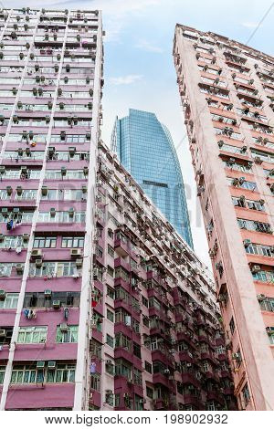 A modern skycraper rises above crowded housing estate in Hong Kong's old residential district of Quarry Bay. With a population of over 7 million Hong Kong is one of the most densely populated areas in the world. Vertical orientation.