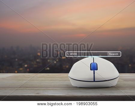 Search www button with wireless computer mouse on wooden table over blur of cityscape on warm light sundown Searching system and internet concept