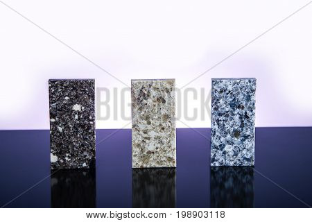 Granite, Granite counter tops. Kitchen granite counter samples. Three granite counter top stones on glossy surface