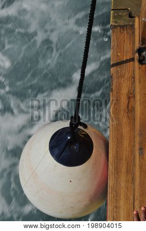 The crumpling dangling on the rope on the wharf of the ship during the mooring.
