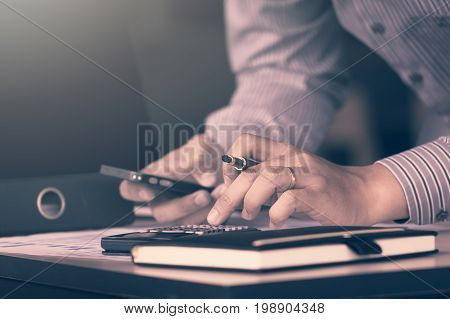 Businessman Calculate About Financial Report And Using Moblie Phone For Searching Data Result In Roo