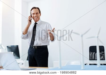 Great plans. Charming smiling man standing in the office and talking on the phone while discussing the project of wind power station and looking at the wind turbine models