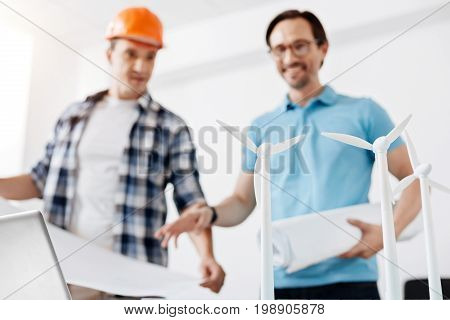 Pleased by their brainchild. Pleasant young builder in an orange hard hat and his colleague-architect looking at the wind power station model, being pleased by the result