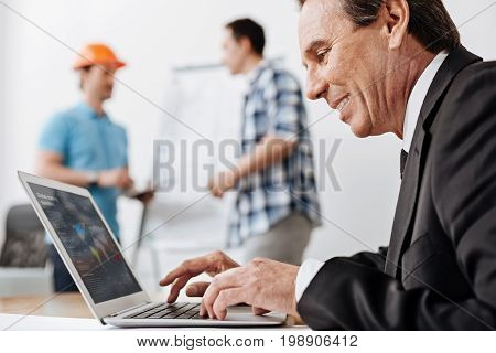 Work with smile. Pleasant smiling senior man in a suit sitting at the table and working on the laptop while his colleagues discussing a blueprint near the whiteboard