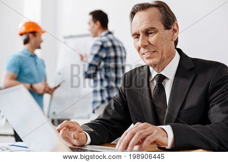 Fast web surfing. Handsome senior man in a suit sitting at the table, and browsing information via his laptop while his colleagues socializing near a whiteboard in the background