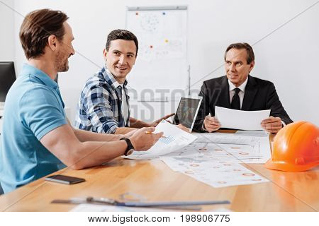 Comprehensive report. Dark-haired young bristled man holding printouts with charts and reporting to his colleagues during the weekly meeting while they listening to him attentively
