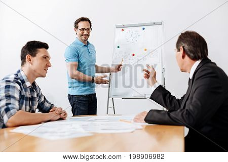 Inspirational talk. Pleasant bristled man giving a speech near the whiteboard and pointing at the printouts pinned on it while his colleagues actively reacting to his words