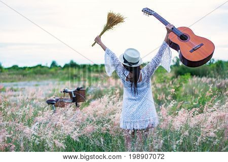 Bicycle with a basket and a woman holding a guitar pick flowers in the meadow and soft focus.