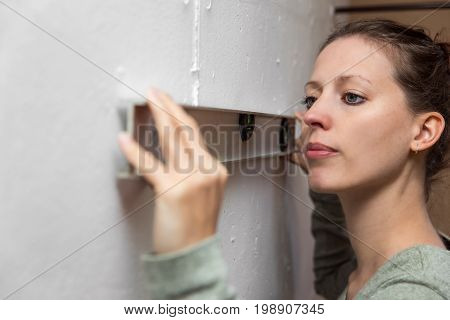 Young Woman Using A Bubble Level On The Wall