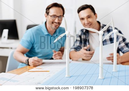 Well done. The focus being on a recently built wind power station model being looked at by two pleasant smiling colleagues sitting at the table