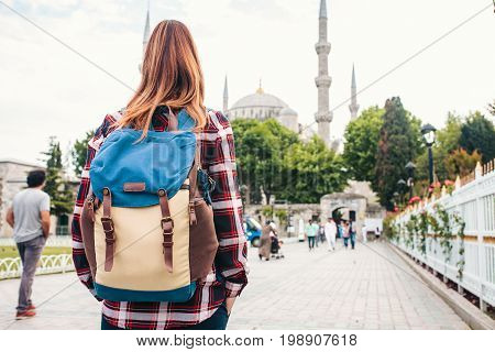 Young beautiful girl traveler with a backpack looking at a blue mosque - a famous tourist attraction of Istanbul. Travel, sightseeing.