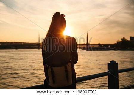 Young beautiful tourist girl with a backpack at sunset next to the Bosphorus on the background of Istanbul. Rest, vacation, hiking.