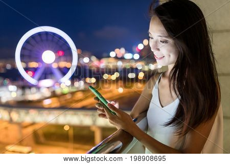 Woman senidng sms on cellphone at night