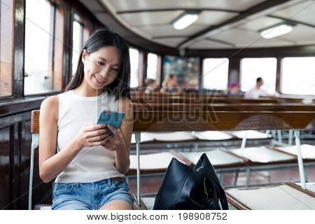 Woman using mobile phone inside ferry