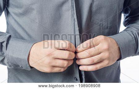 Men putting on his shirt close up. Men's hands buttoning the shirt