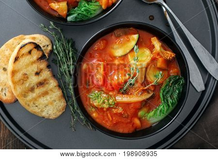 Two bowl of soup minestrone with seasonal vegetables close up top view. Italian food