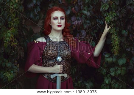 Portrait of a red-haired woman warrior in her hands she holds a sword.