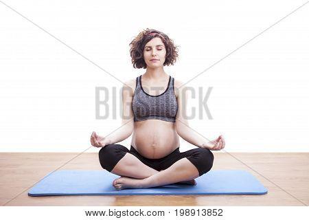 Young pregnant woman doing yoga on matt.