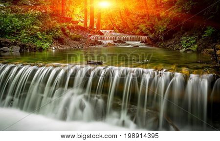 Summer landscape with sunset over waterfall in forest