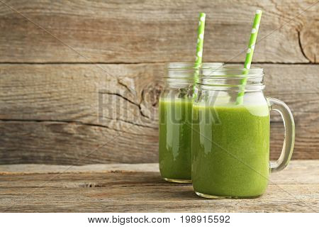 Bottles Of Juice With Cucumber, Celery And Broccoli On Grey Wooden Table