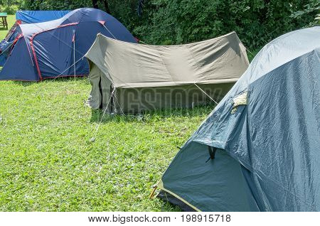 Several different tents standing in a row in the open glade tourist town.