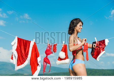 New year girl on sunny blue sky. Santa claus girl hanging clothes for drying. Xmas red costume on rope with pin. Laundry and dry cleaning. Christmas woman with happy face outdoor.