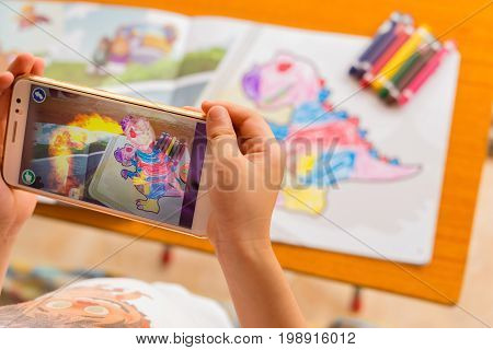 ZhongshanChina-August 8 2017:kid playing Augmented Reality popup paintings of a filled dinosaur via mobile. AR and VR games become more and more popular.