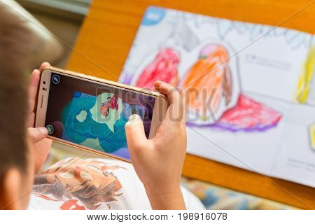 ZhongshanChina-August 8 2017:kid playing Augmented Reality popup paintings of a filled penguin via mobile. AR and VR games become more and more popular.