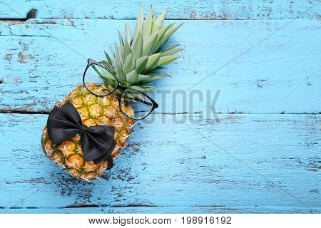 Ripe Pineapple With Glasses And Bow Tie On Blue Wooden Table