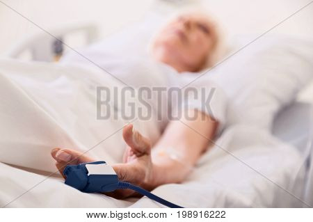Under control. Delicate sick senior woman wearing special device which measuring her heart rate while lying in bed in hospital