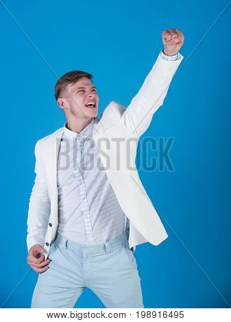 Businessman celebrating achievement on blue background. Man shouting with winner gesture. Victory and reward concept. Business and success. Manager wearing white jacket shirt and pants.