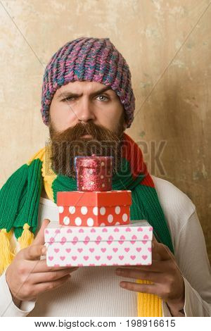 Guy with sad face and gift pack. Hipster with present box in hat. Holiday celebration and shopping. Christmas and birthday. Man with long beard in colorful scarf.