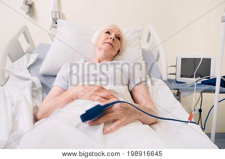 Improving condition. Ailing bright aged lady resting on a bed while recovering and restoring her strength after recent heart attack