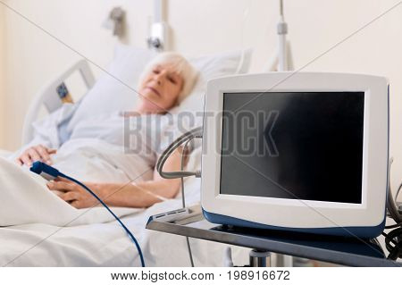 Specific apparatus. Fragile ill senior woman wearing a device on her finger which tracking her heart rate while sleeping in hospital bed
