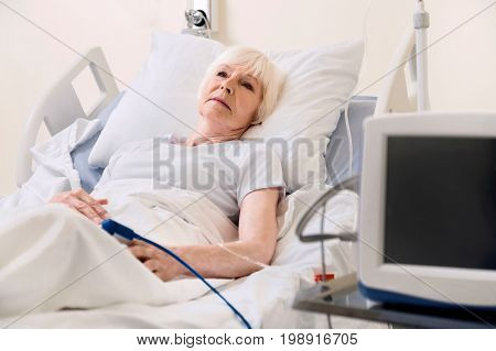 I will get up soon. Sore vulnerable aged lady resting in hospital bed and thinking of something while recovering from recent heart problem